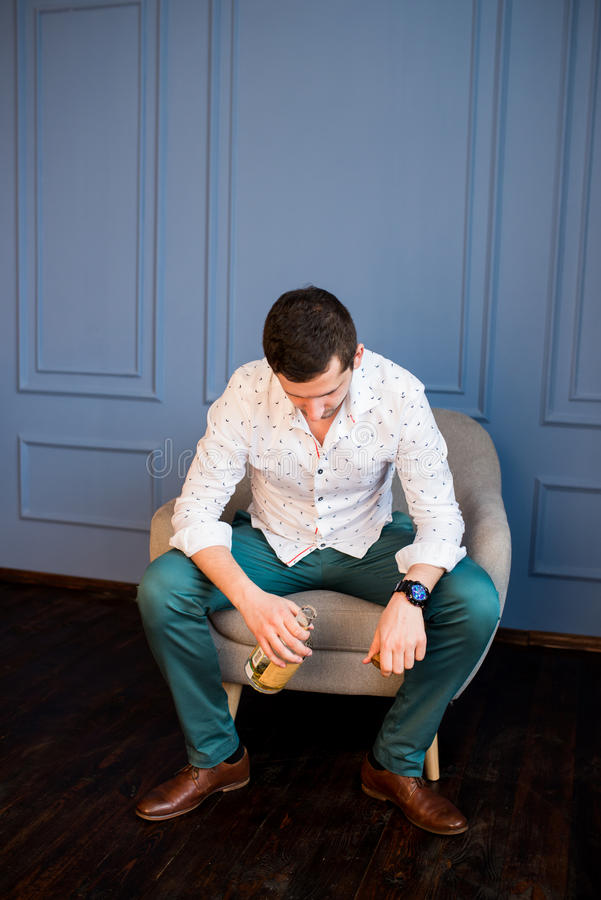 Depressed man drinking whisky sitting in armchair stock photography