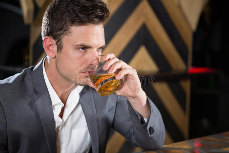 Depressed man having glass of whisky at counter royalty free stock photo