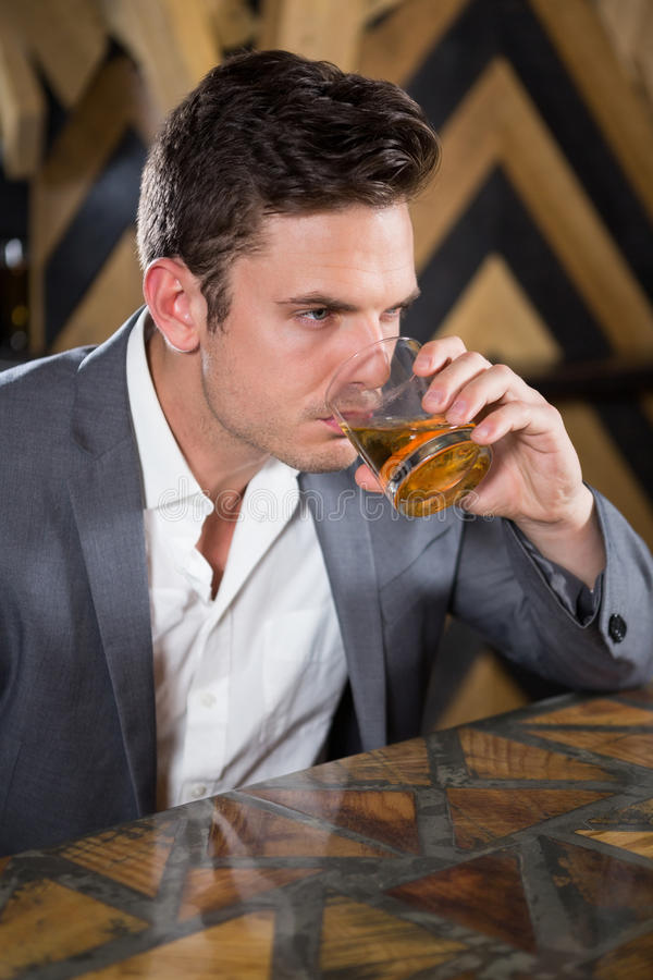 Depressed man having glass of whisky at counter royalty free stock photos