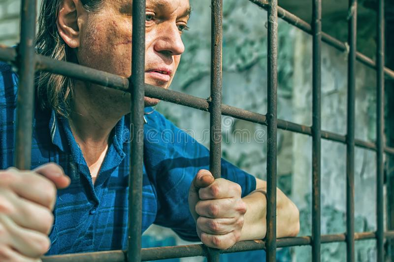 A depressed man holds his hands on the prison bars. Prisoner for the crime. Poor conditions. Scream, despair, pain, hunger stock photos