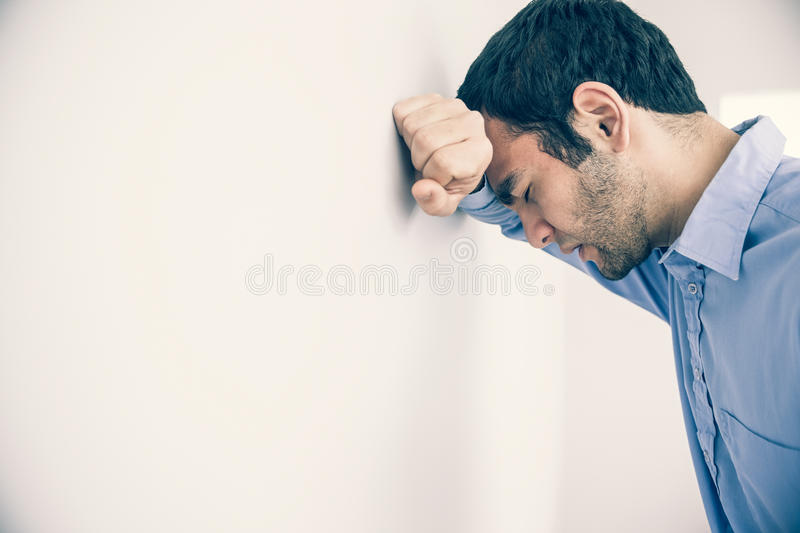 Depressed man leaning his head against a wall. Depressed man with fist clenched leaning his head against a wall royalty free stock photography