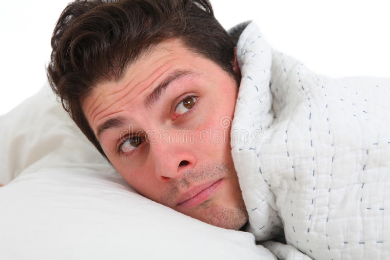 Depressed man lying in bed stock image