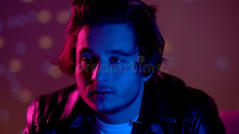 Depressed man relaxing on party in night club, thinking over life problems. Stock photo stock photography