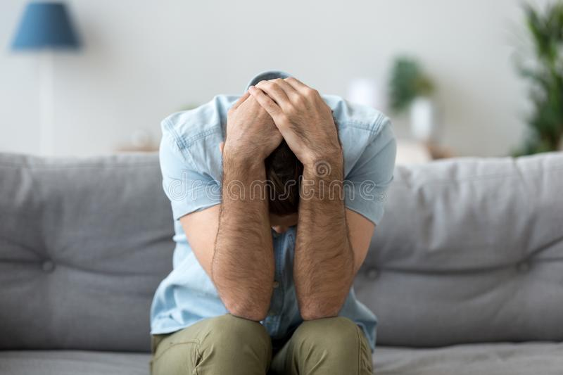 Depressed man sit on couch suffering from life problems. Depressed man sitting on couch at home holding head in hands suffering from headache or dizziness stock photos