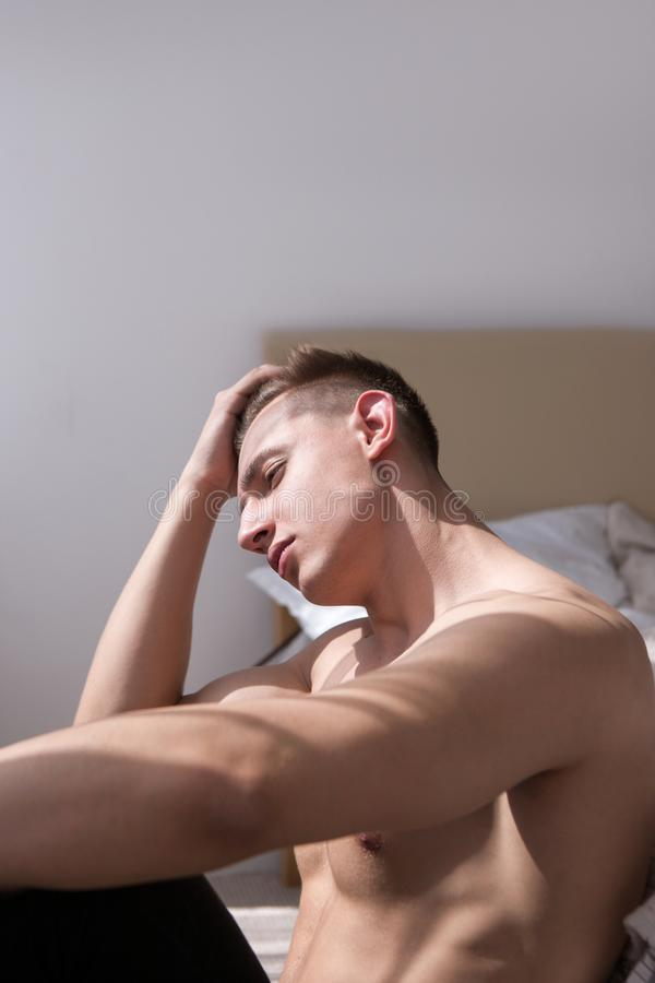 Depressed man sitting nearby bed concept stock photography