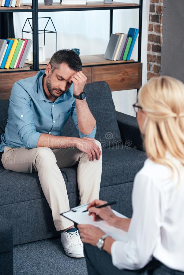 depressed man sitting on sofa while female psychiatrist writing in clipboard royalty free stock photos