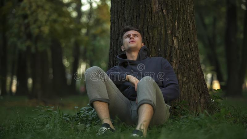 Depressed man sitting under tree in park, unemployment problem, difficulties. Stock photo royalty free stock photos