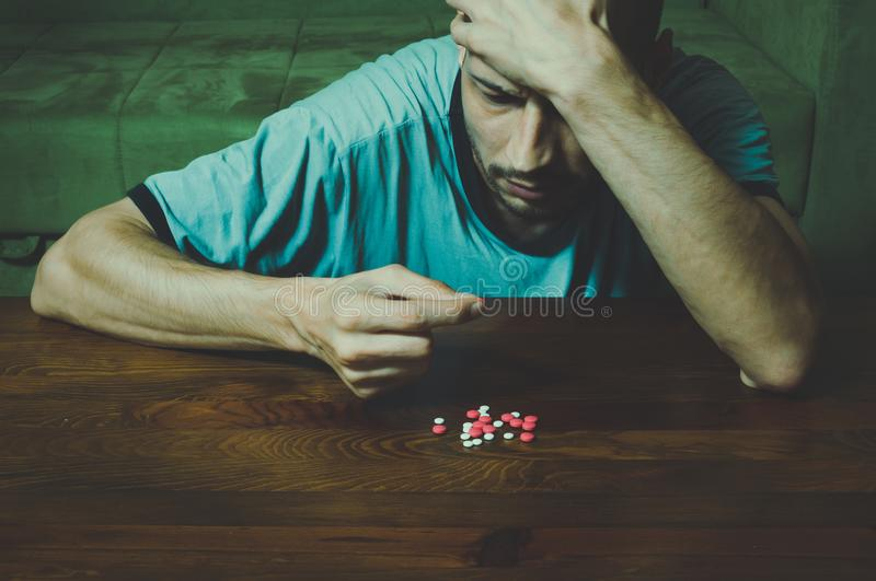 Depressed man suffering from suicidal depression want to commit suicide by taking strong medicament drugs and pills and he is cove. R his face with his hand royalty free stock image