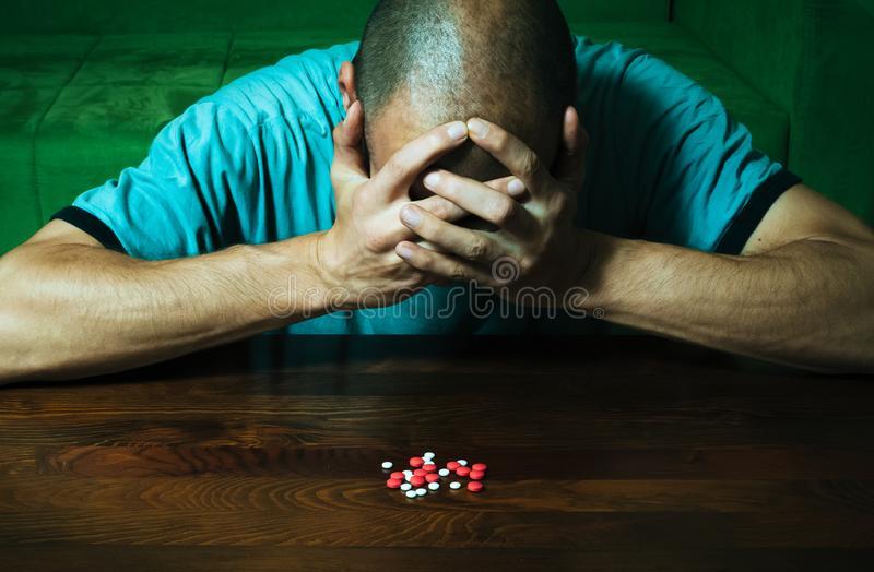 Depressed man suffering from suicidal depression want to commit suicide by taking strong medicament drugs and pills while he is si. Tting on the floor of his stock photography