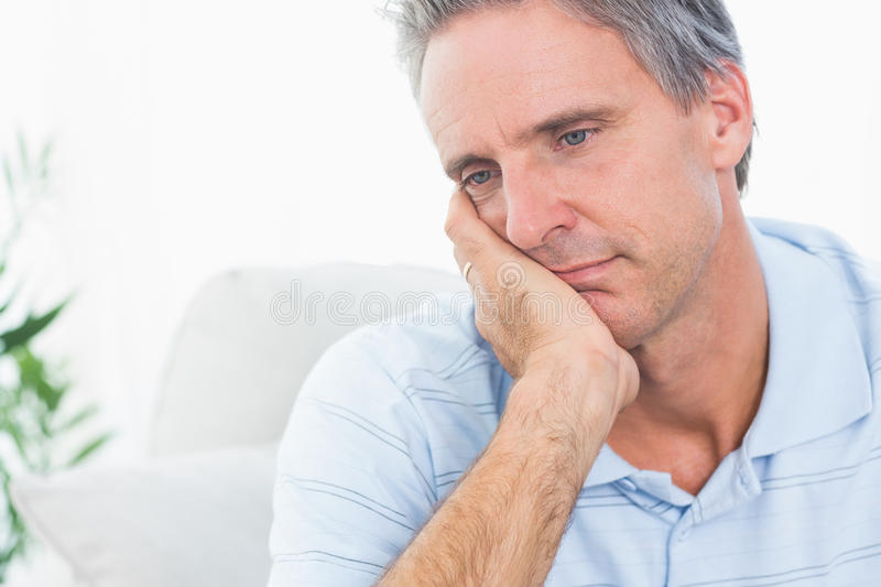 Depressed man thinking. At home on couch royalty free stock photo