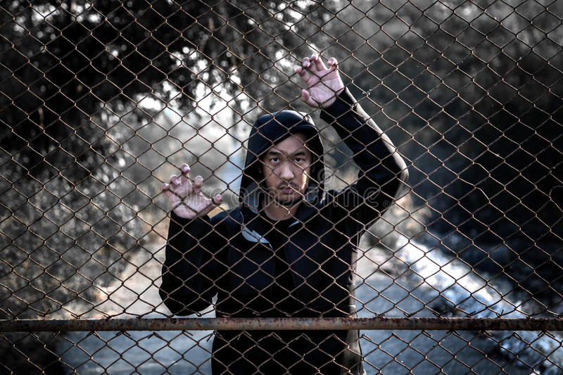 Depressed man wearing a black hoodie standing behind a fence han. D grabs steel mesh cage, no freedom royalty free stock photography