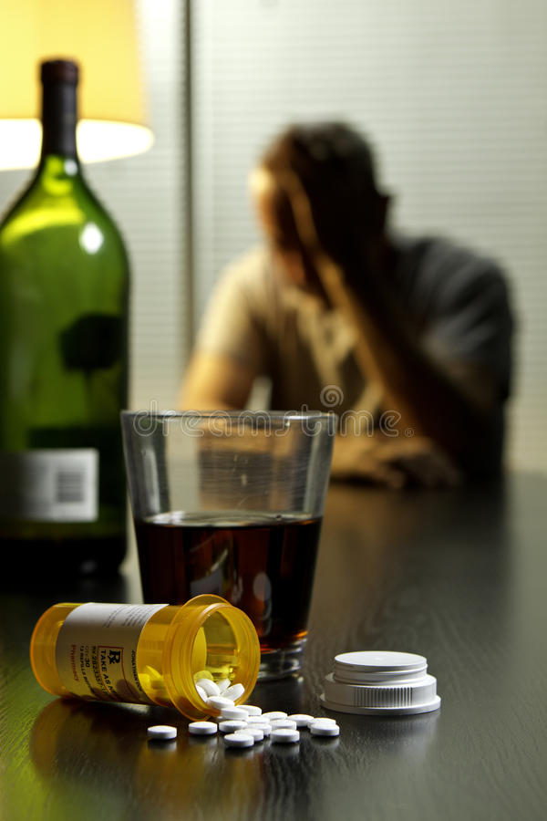 Depressed man with wine and prescription pills, vertical royalty free stock images