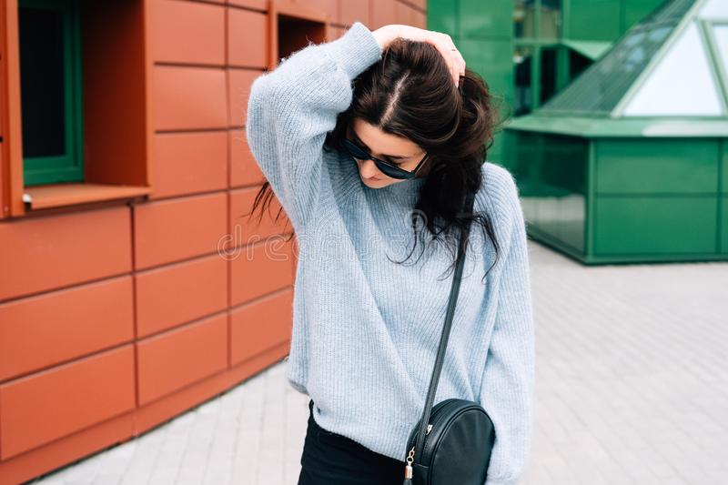 Depressed millennial woman in sunglasses in city street. Loneliness and sadness concept. Urban style.  royalty free stock images