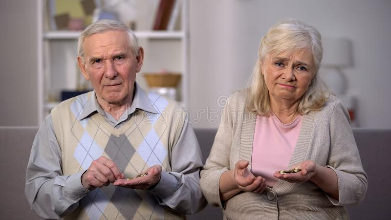 Depressed old people holding coins looking camera, pension age increase, poverty. Stock photo stock photography