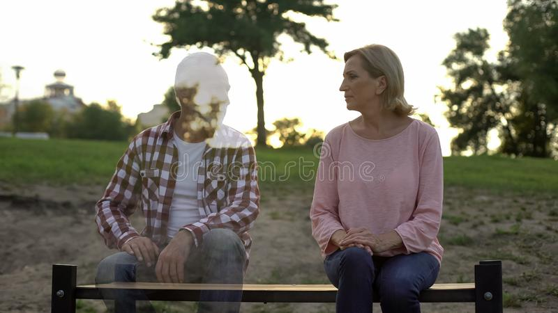 Depressed old woman sitting on bench, husband appearing beside, loss, memories royalty free stock photos