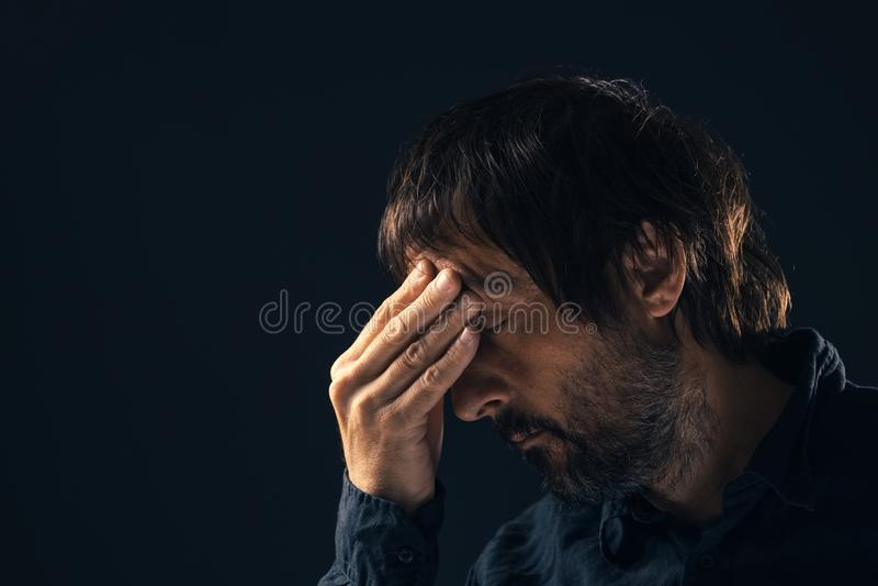 Depressed sad mid-adult man portrait. Depressed sad mid-adult man. Low key portrait of male person feeling heartbroken. Distraught state of mind and mental stock images