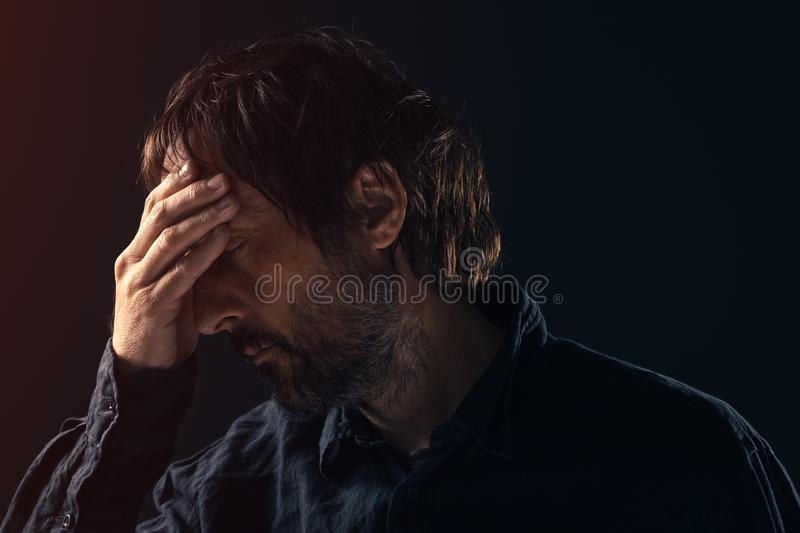 Depressed sad mid-adult man portrait. Depressed sad mid-adult man. Low key portrait of male person feeling heartbroken. Distraught state of mind and mental stock photography