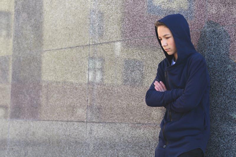 Depressed sad teenage boy on a dark background, teenage problem concept.  royalty free stock photography