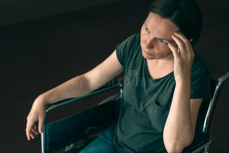 Depressed sad woman in worn wheelchair looking out the window stock image