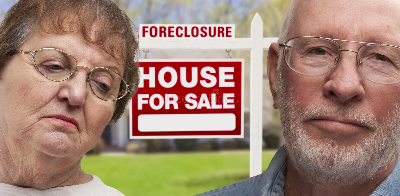 Depressed Senior Couple in Front of Foreclosure Sign and House. Depressed Senior Couple in Front of Foreclosure Real Estate Sign and House stock photos