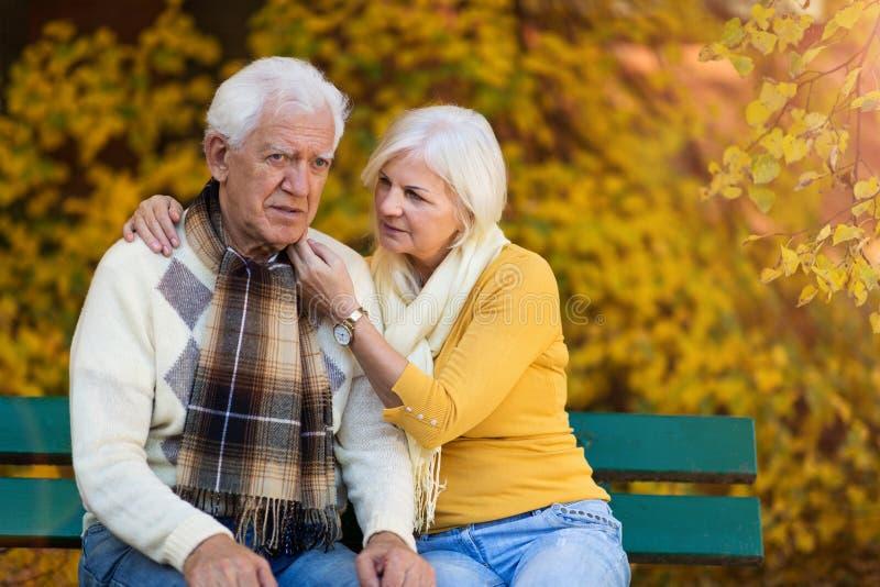 Depressed senior man consoled by elderly woman stock image