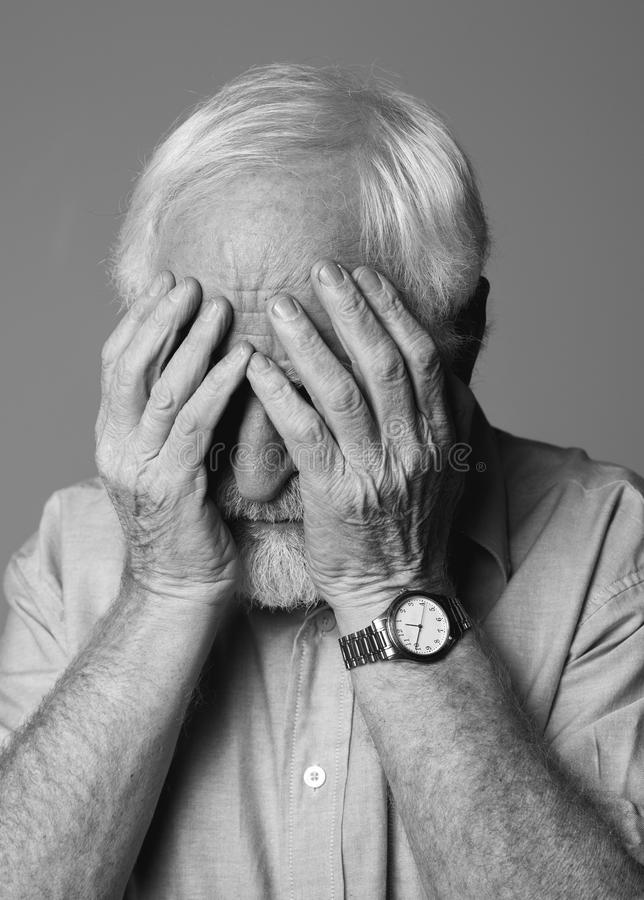 Depressed senior man covering face with hands royalty free stock images