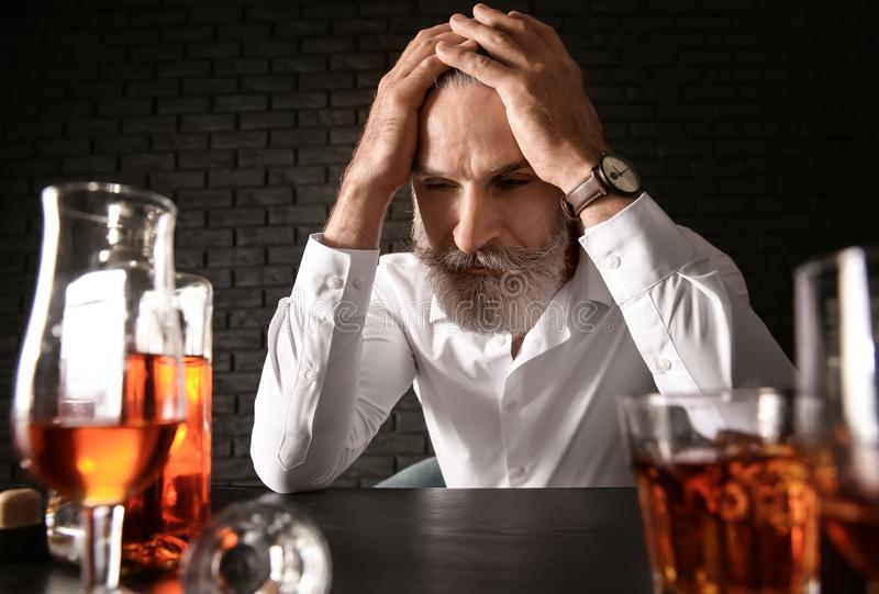 Depressed senior man drinking whiskey at table on dark background royalty free stock image