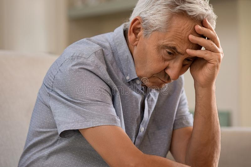 Depressed senior man at home stock photo