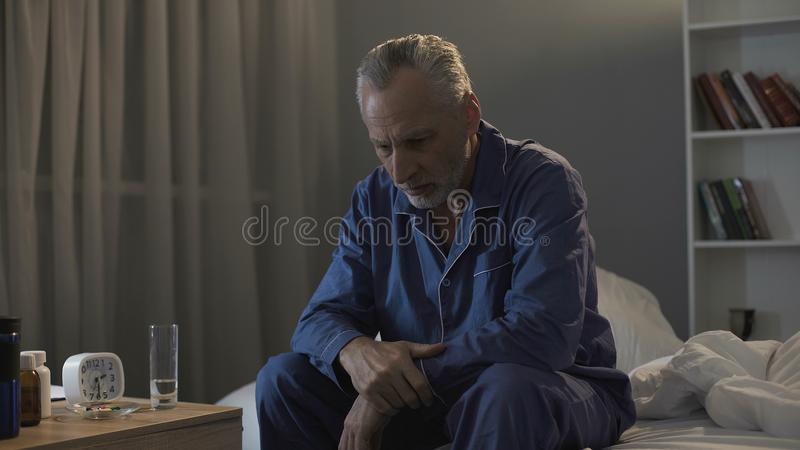 Depressed senior person sitting in bed and suffering from insomnia, health stock images