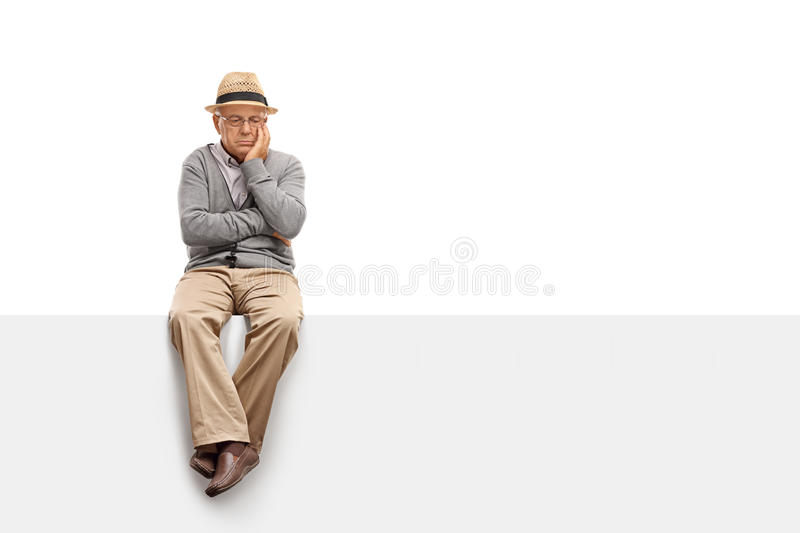 Depressed senior sitting on a panel stock image