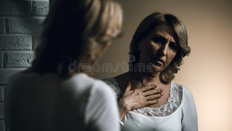 Depressed senior woman looking at reflection in mirror, skin cancer, worries stock photos