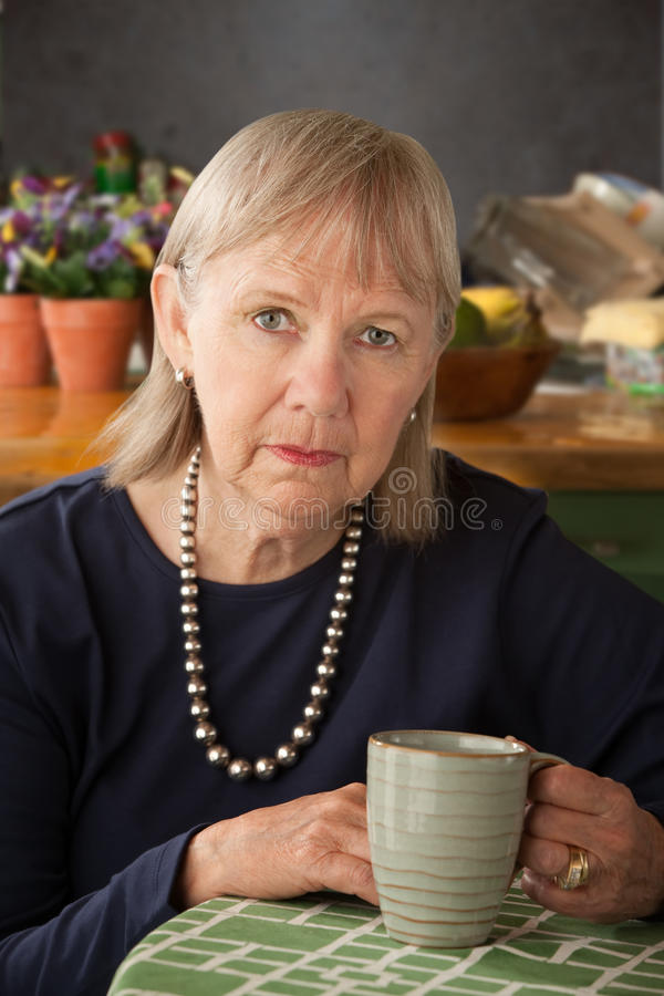 Depressed senior woman with mug stock images