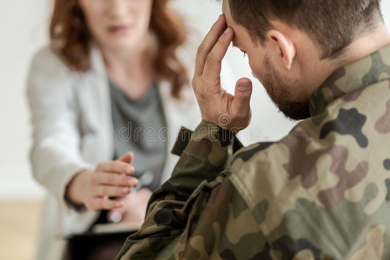 Depressed soldier with suicidal thoughts wearing green uniform during therapy with psychiatrist. Concept stock photography