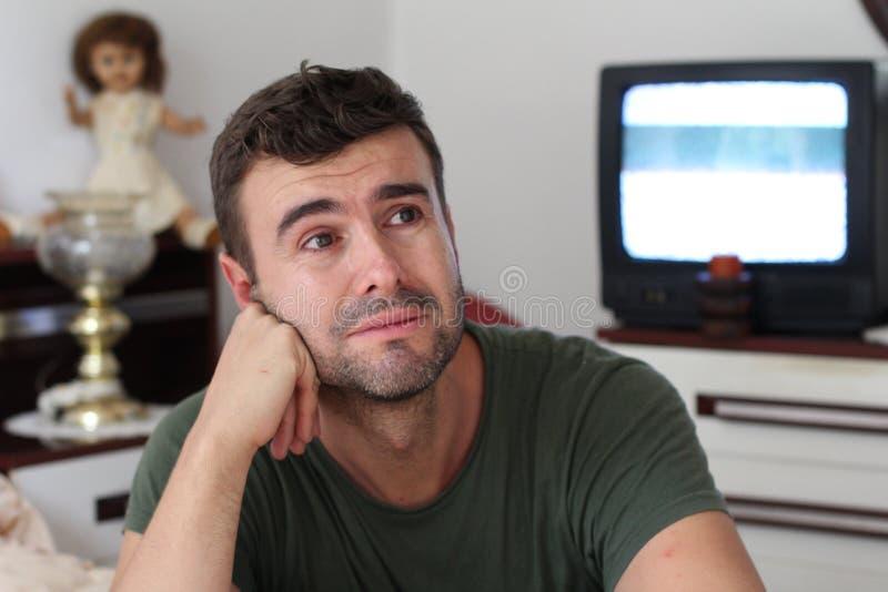 Depressed som ser mannen som hemma gråter royaltyfria foton