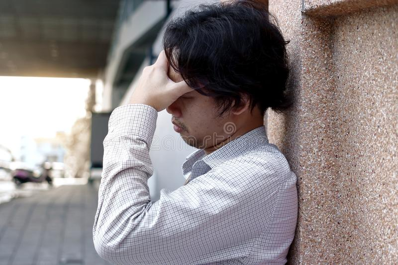 Depressed and stressed Asian business man with hands on forehead leaning on the wall stock image