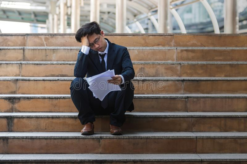 Depressed stressed young Asian business man in suit with hands on head sitting on stairs. Unemployment and layoff concept royalty free stock images