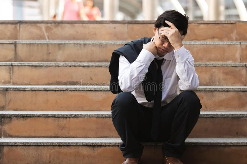 Depressed stressed young Asian business man in suit with hands on head sitting on stairs. Unemployment and layoff concept stock image