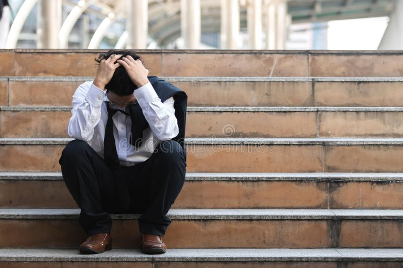 Depressed stressed young Asian business man in suit with hands on head sitting on stairs. Unemployment and layoff concept stock photos