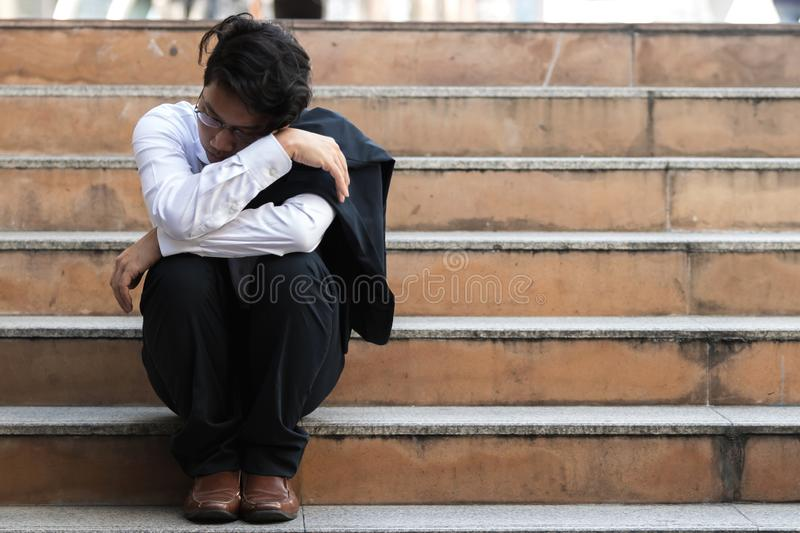 Depressed stressed young Asian business man in suit suffering from severe depression sitting on stairs. Unemployment and layoff stock image