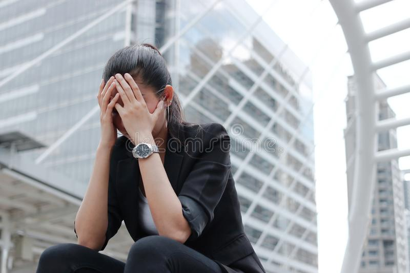 Depressed stressed young Asian business woman covering face with hands suffering from trouble.  royalty free stock photos