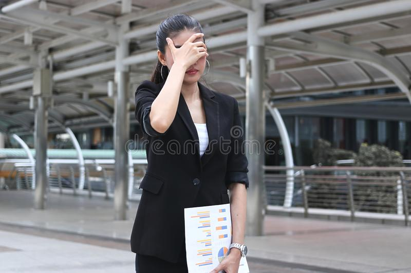 Depressed stressed young Asian business woman covering face with hands suffering from trouble.  stock image