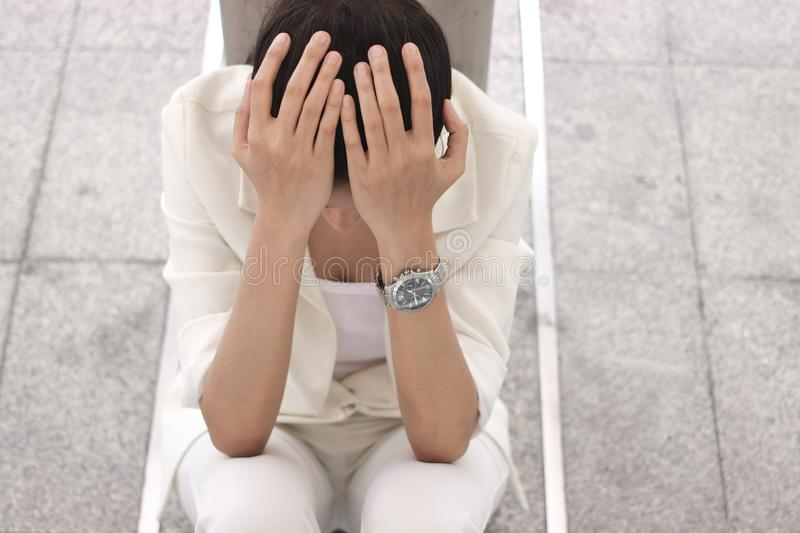Depressed stressed young Asian business woman covering face with hands suffering from trouble royalty free stock image