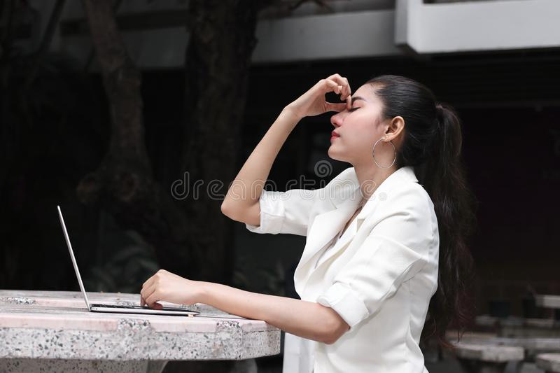 Depressed stressed young Asian business woman covering face with hands suffering from trouble stock images