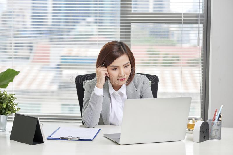 Depressed stressed young Asian business woman with laptop suffering from trouble stock image