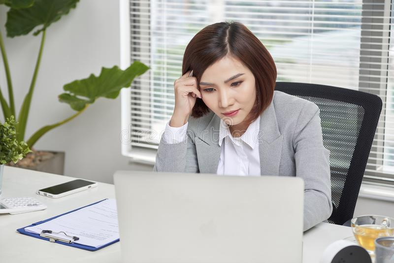 Depressed stressed young Asian business woman with laptop suffering from trouble stock photo