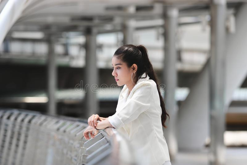 Depressed stressed young Asian business woman suffering from trouble at outside office.  royalty free stock images