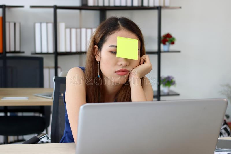 Depressed stressed young Asian employee with post its on the face sitting on the workplace in office stock photos