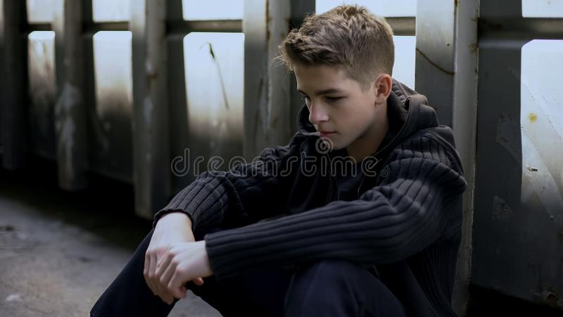 Depressed teen feeling lonely, sitting in abandoned house, no support and care stock images