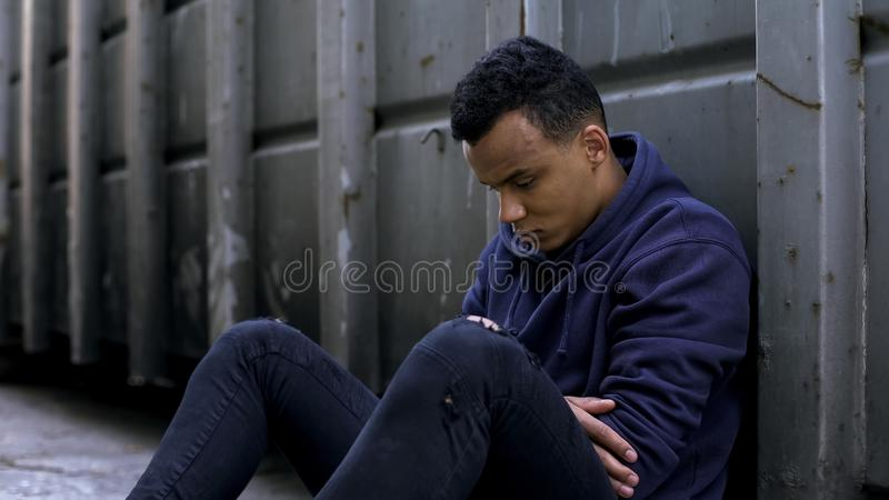 Depressed teenager sitting in gateway, lost child, escape from parents, problem. Stock photo royalty free stock images
