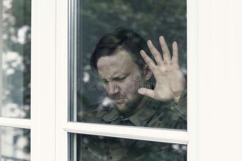 Depressed and tired soldier with war syndrome and violence problem royalty free stock photography